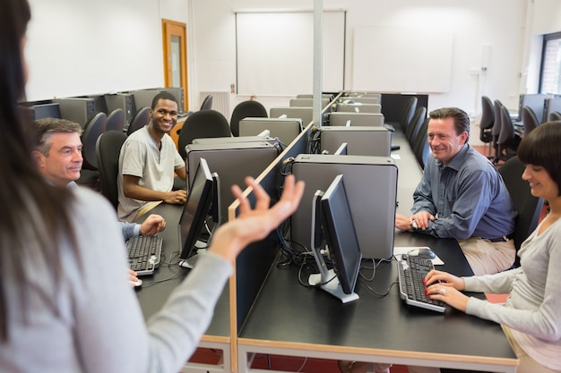 Teacher talking to group in computer room Premium Photo