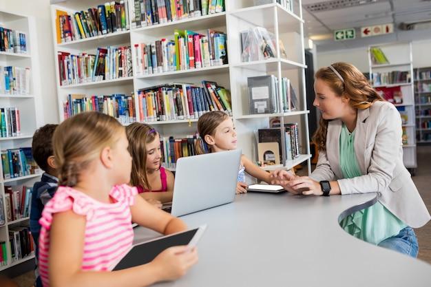 Teacher using computer with pupils Premium Photo