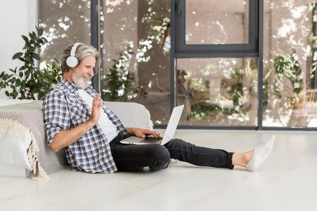 Insegnante che per mezzo del computer portatile che si siede sul pavimento Foto Gratuite