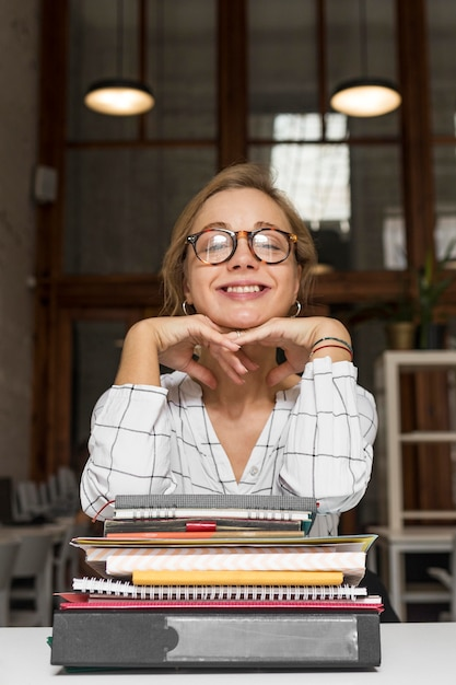 Teacher with elbow on stack on books Free Photo