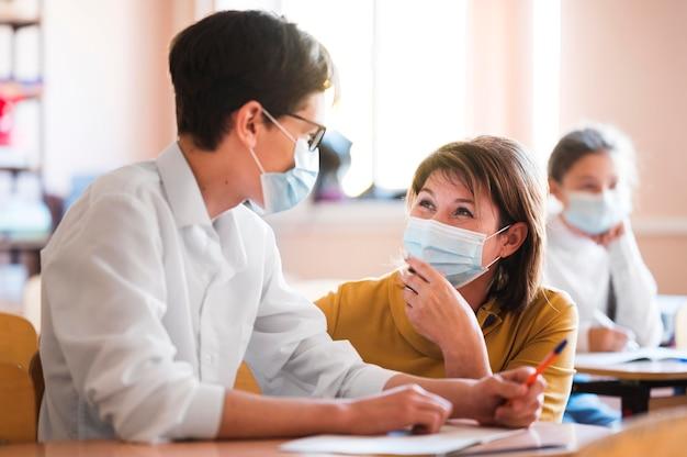 Teacher with mask explaining class Free Photo
