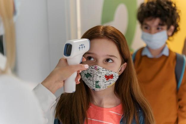 学校で子供の体温をチェックする医療用マスクを持った先生 無料写真