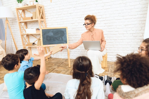 Teacher with spectacles gives book to student sitting on floor Premium Photo