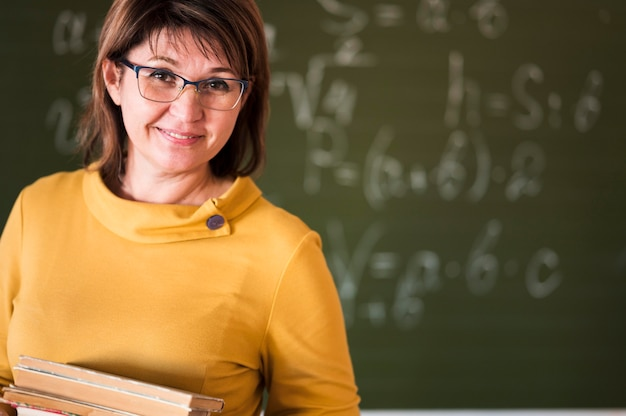 Teacher with stack of books in claass Free Photo