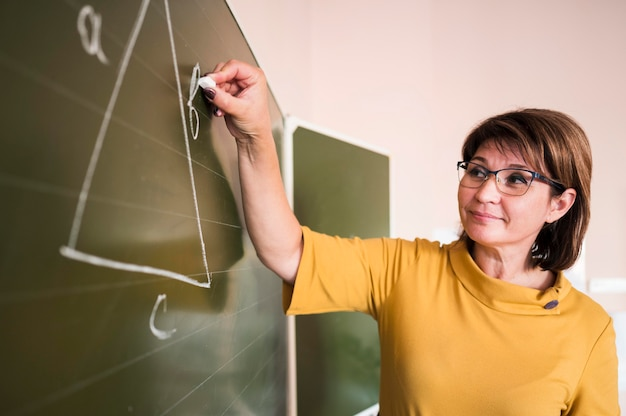 Teacher writing at chalkboard Free Photo