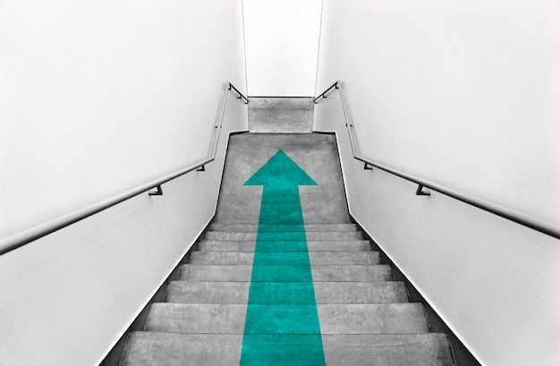 Teal arrow on gray staircases Free Photo