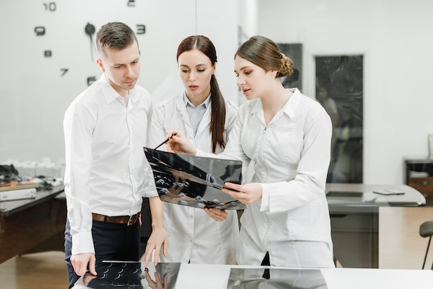 Team of doctors examining x-ray of a patient Premium Photo