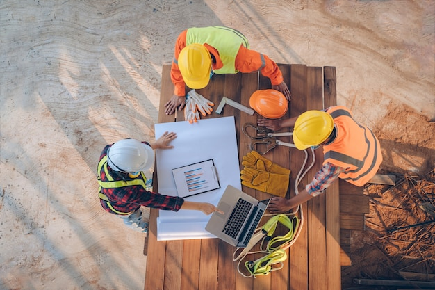 Team of engineer and architects working, meeting, discussing,designing, planning, measuring layout of building blueprints at construction site,top view,construction concept. Premium Photo