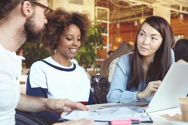 Team che si riunisce in uno spazio di coworking, discute di piani e vision, crea nuove soluzioni e strategie aziendali utilizzando il laptop. Foto Gratuite