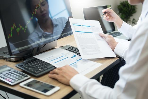 Team investment entrepreneur обсуждает и анализирует торговые графики и графики на компьютере Premium Фотографии