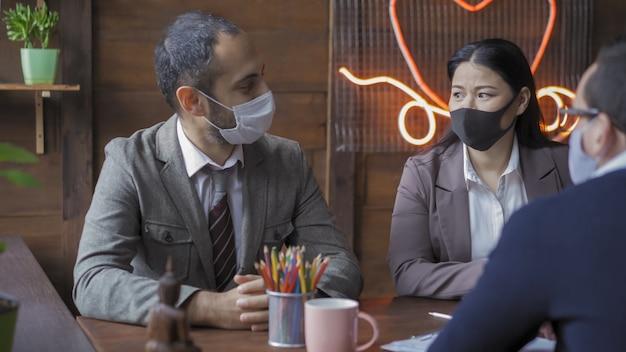 Команда деловых людей занята работой в команде во время вспышки коронавируса. Premium Фотографии