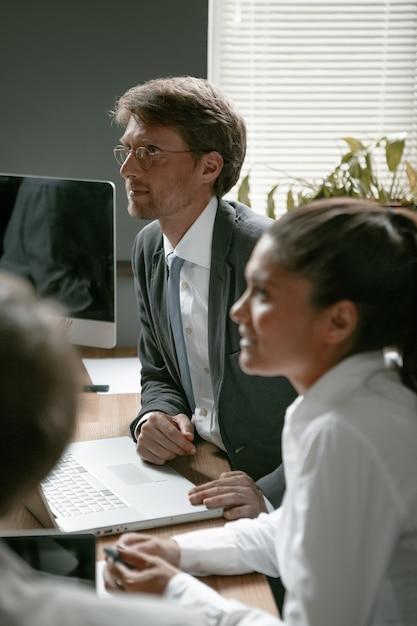 ビジネスマンのチームはオフィスで働いています。見ている眼鏡の白人男性に選択的な焦点 Premium写真