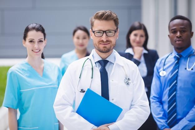 병원 구내에 함께 서있는 의사 팀 무료 사진