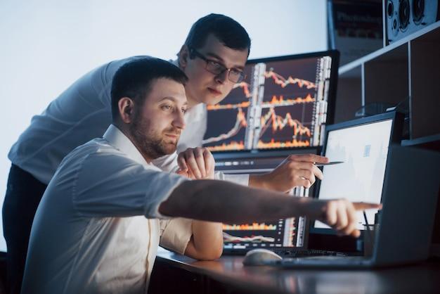 Команда биржевых маклеров разговаривает в темном офисе с экранами. анализ данных, графиков и отчетов для инвестиционных целей. креативная работа трейдеров Бесплатные Фотографии