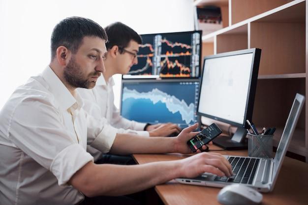 株式仲買人のチームが、ディスプレイ画面のある暗いオフィスで会話しています。投資を目的としたデータ、グラフ、レポートの分析。クリエイティブチームワークトレーダー 無料写真