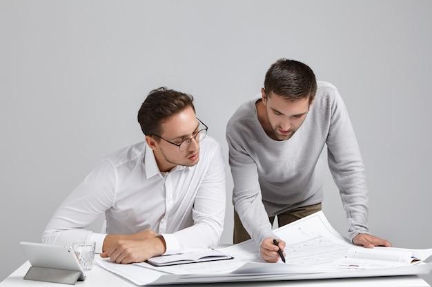 현대 사무실 인테리어에 건설 계획을 확인 두 잘 생긴 세련된 젊은 수염 유럽 남성 빌더 팀 무료 사진