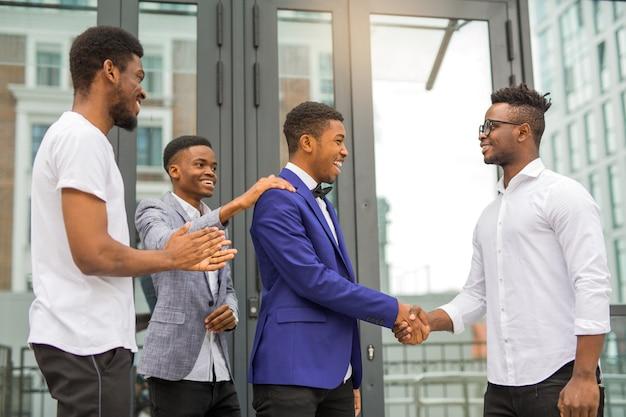 Команда молодых африканцев возле здания пожимает друг другу руки Premium Фотографии