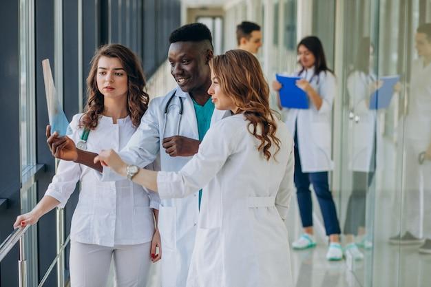 Команда молодых специалистов-врачей, стоящих в коридоре больницы Бесплатные Фотографии