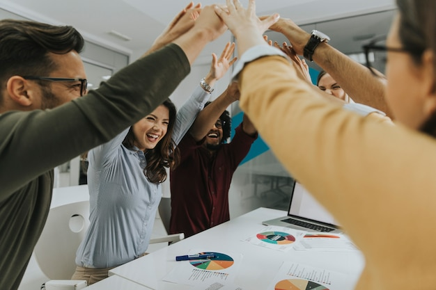 Team people stacking hands together over table engaged in teambuilding Premium Photo