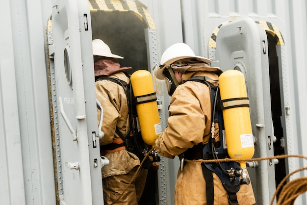 Team of sea firefighters on a training how to stop fire in a dangerous mission Premium Photo