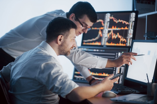 Team of stockbrokers are having a conversation in a dark office with display screens. analyzing data, graphs and reports for investment purposes. creative teamwork traders Premium Photo