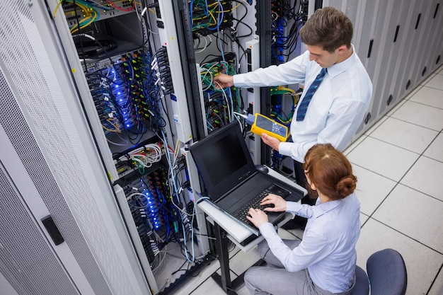 Team of technicians using digital cable analyser on servers Premium Photo
