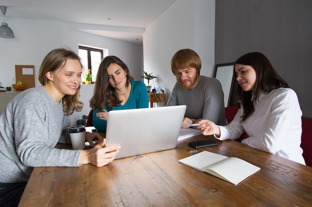 Team watching presentation at meeting table Free Photo