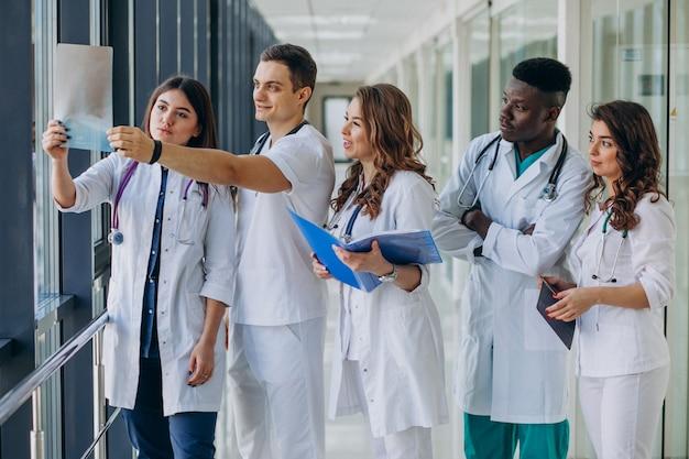 Team di giovani medici specialisti in piedi nel corridoio dell'ospedale Foto Gratuite