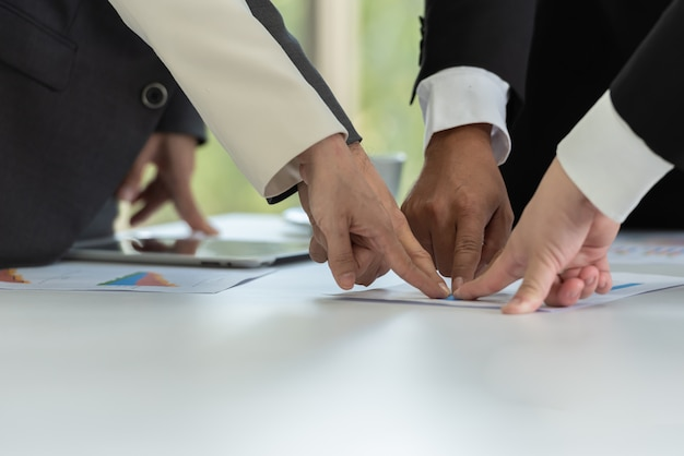 Teamwork of business people finger to the target together in the meeting. Premium Photo
