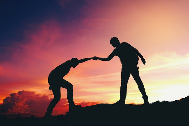 Teamwork couple helping hiking each other silhouette on mountains Premium Photo