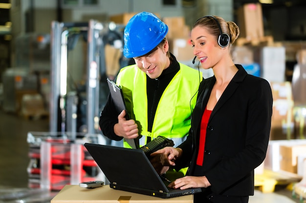Teamwork, warehouseman or forklift driver and female supervisor with laptop, headset and cell phone, at warehouse of freight forwarding company  a forklift Premium Photo