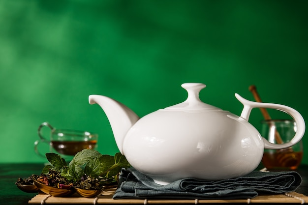 Teapot in arrangement with aromatic herbs Free Photo