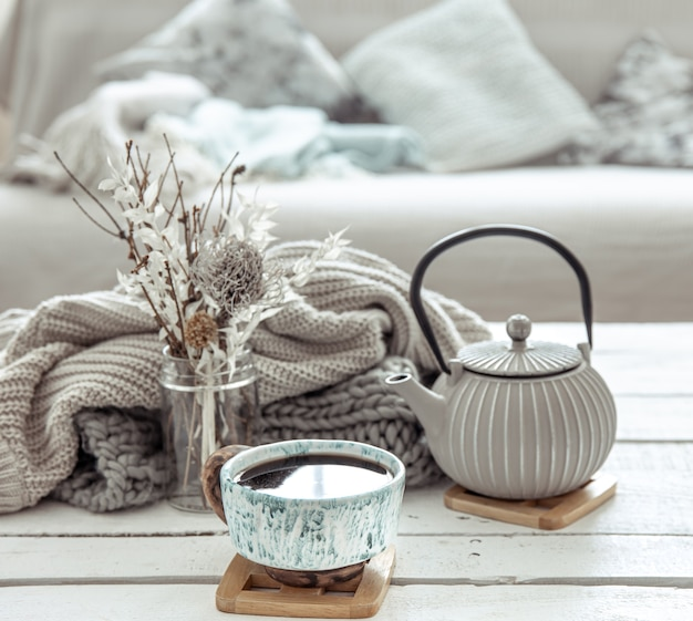 A teapot and a beautiful ceramic cup with decor details in a hygge style living room Free Photo