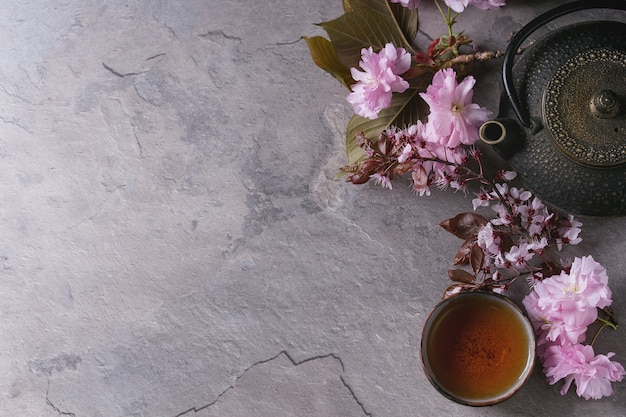 Teapot and cup of tea with blossom branch Premium Photo