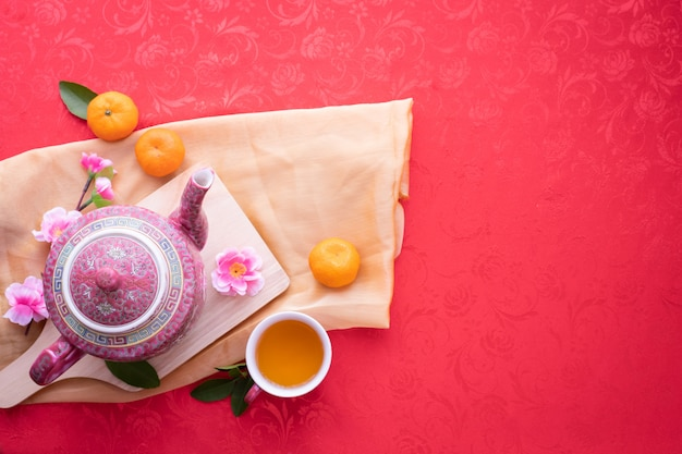 Teapot and cup of tea with cherry blossom on red background Premium Photo