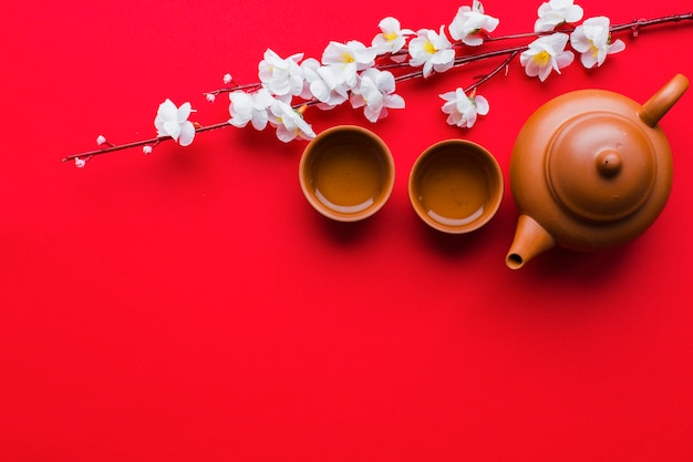 Teapot and cups near cherry branch Free Photo