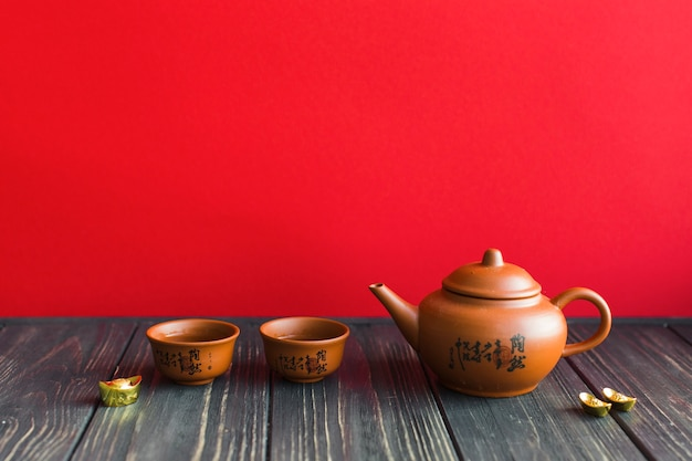 Teapot and cups on wooden tabletop Free Photo