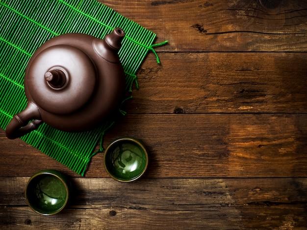 Teapot on green bamboo mat. top view Premium Photo
