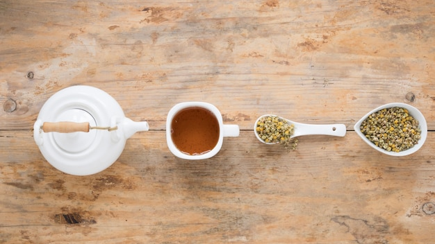 Teapot; lemon tea and dried chinese chrysanthemum flowers arranged in a row on table Free Photo
