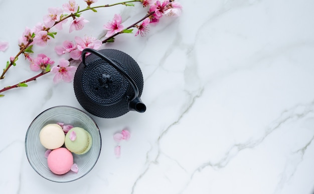 Teapot and macarons with flowers on marble background. Premium Photo