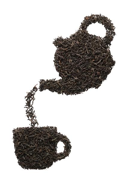 Чайник наливает чай в чашку. силуэт из сухих листьев черного чая. изолированный. Premium Фотографии