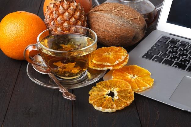 紅茶、バラ、オレンジ、グレープフルーツの明るい背景とティーポット Premium写真