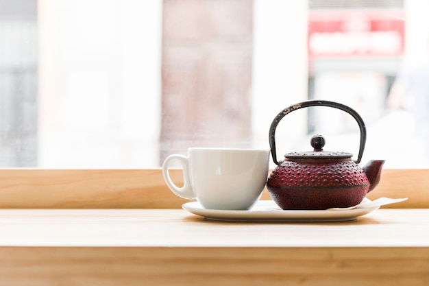 Teapot with white tea cup on wooden desk Free Photo