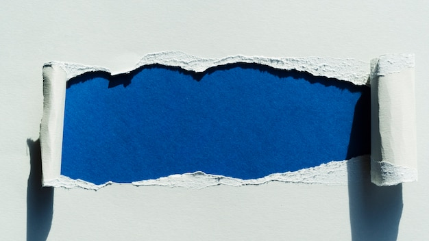 Tear in paper with blue color Premium Photo