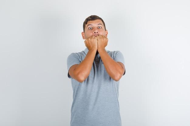 Uomo del servizio tecnico che si morde i pugni in maglietta grigia e sembra nervoso Foto Gratuite