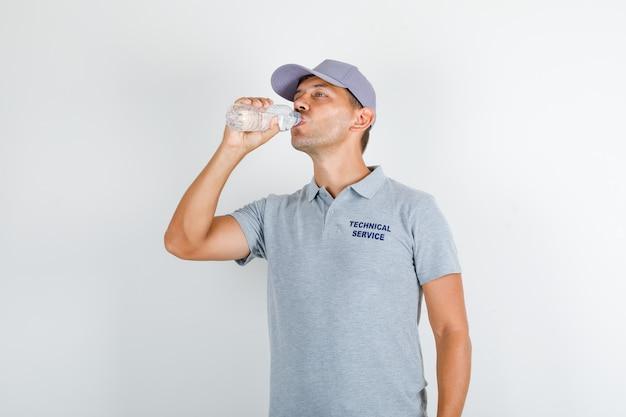 Acqua potabile dell'uomo di servizio tecnico in maglietta grigia con il cappuccio Foto Gratuite