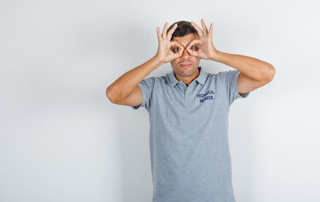 Technical service man in grey t-shirt showing glasses gesture and looking funny Free Photo