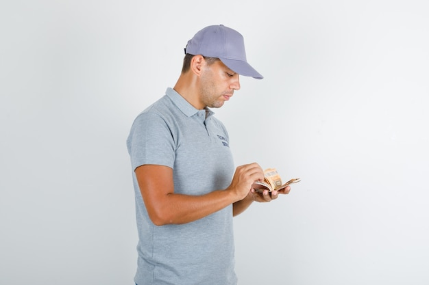 Technical service man in grey t-shirt with cap counting euro banknotes Free Photo