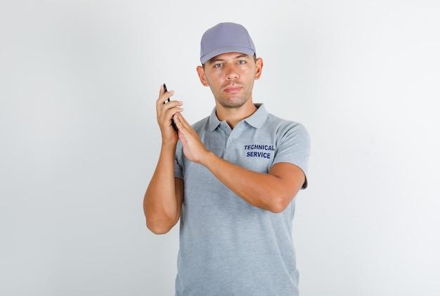 Uomo di servizio tecnico in maglietta grigia con cappuccio che copre il microfono sullo smartphone Foto Gratuite