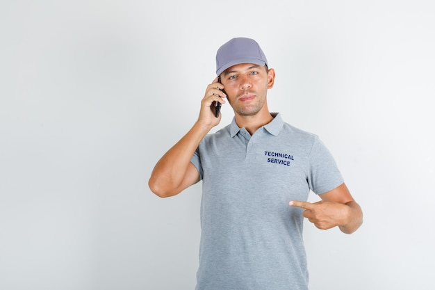 Technical service man in grey t-shirt with cap holding smartphone and showing himself Free Photo